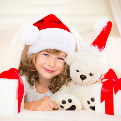 Child and teddy with Christmas gift. Xmas holiday concept
